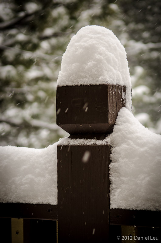 Snow covered fence post