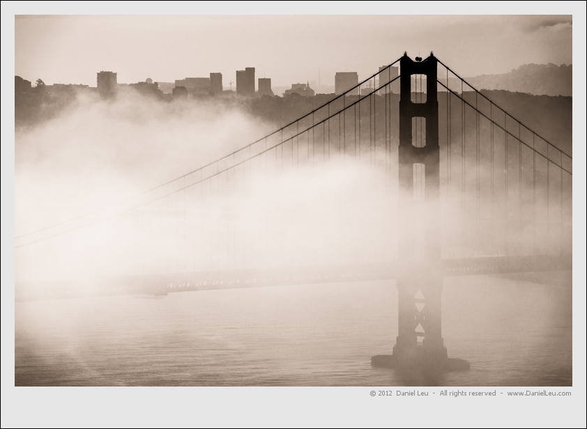 Golden Gate Bridge tower and San Francisco skyline with a patch of fog