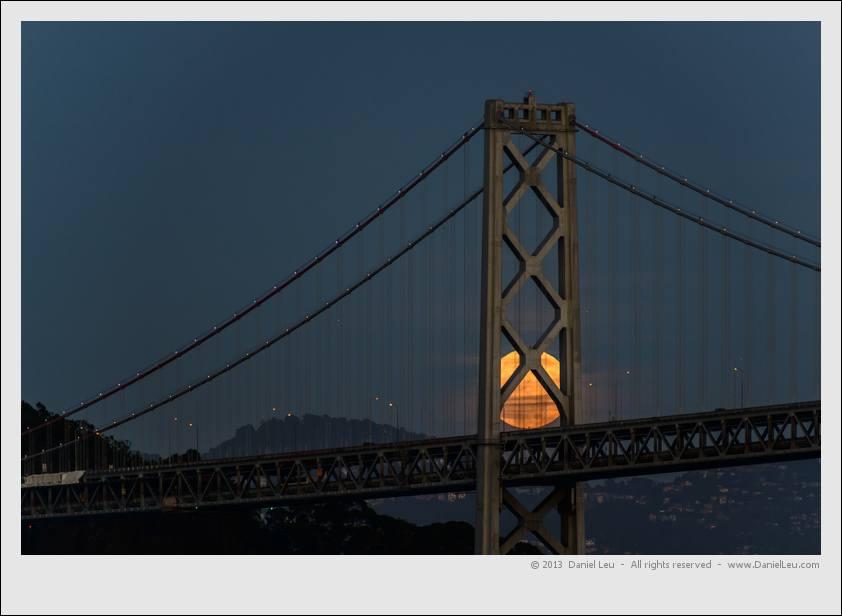 Full moon 'hiding' behind San Francisco Bay Bridge tower.