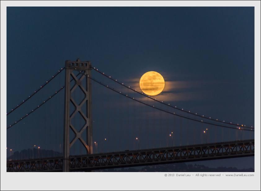 Full moon dancing on Bay Bridge suspension cables